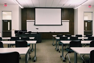 empty classroom with white desks and black chairs